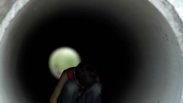 sad lonely boy in deep depression hiding inside of a drainage tunnel, lonely homeless boy video