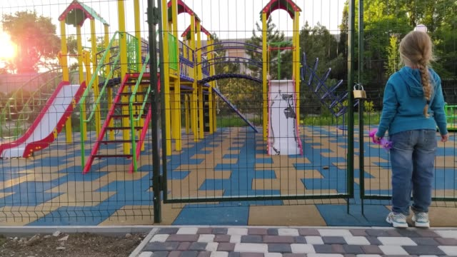 Sad lonely child near the closed playground because of the quarantine.A girl with long blonde braided hair staying alone near empty fenced showground without children.COVID-19 lockdown social distance
