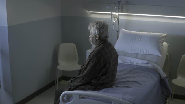 vídeos y material grabado en eventos de stock de triste hombre anciano solitario sentado en una cama de hospital por la noche - geriatría