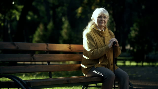 Sad lonely old woman sitting on bench in park, abandoned elderly people alone Sad lonely old woman sitting on bench in park, abandoned elderly people alone park bench stock videos & royalty-free footage