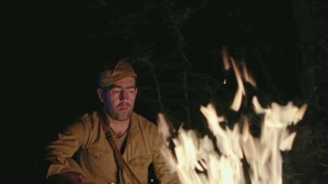 A sad lonely soldier from World War II sits by the fire in the woods and looks sadly at the fire