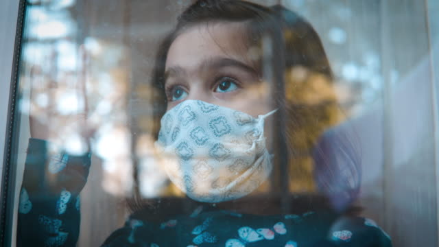 Sad looking little girl with protective mask on her face looking through window because she is not allowed to go outside and play. video