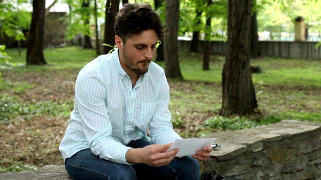 Sad looking male in the park, reading and tearing one letter. video