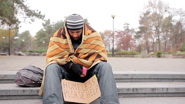 Sad male beggar sitting alone in park, warming up with old blanket, man coughing video