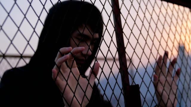 vídeos de stock e filmes b-roll de a sad man behind fence - vício
