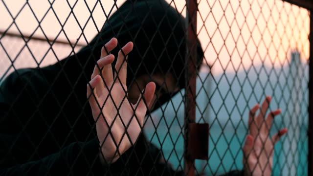 A sad man behind fence