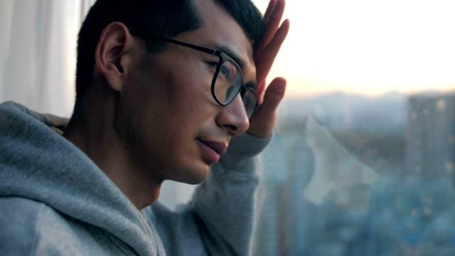 悲しい男は孤独を感じ、窓の外を見る - 悩む点の映像素材/bロール