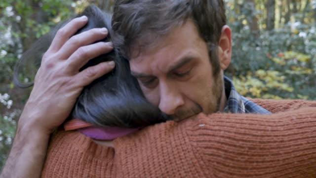 stockvideo's en b-roll-footage met sad man knuffelen een vrouw helpt hem om door middel van een aantal moeilijke tijden - funeral crying