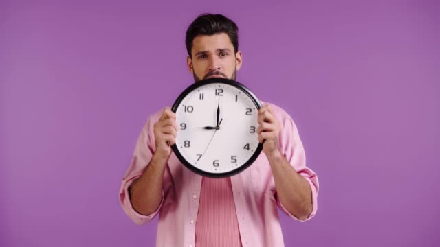 sad man obscuring face with clock isolated on purple sad man obscuring face with clock isolated on purple instrument of time stock videos & royalty-free footage