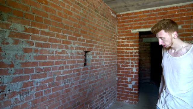 sad man punching against a brick wall - colpire con un pugno video stock e b–roll