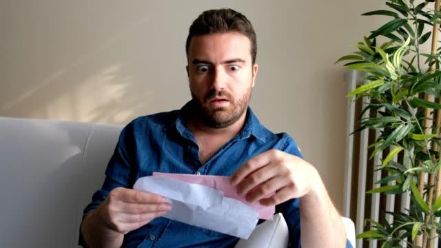 Sad man reading pink slip letter at home
