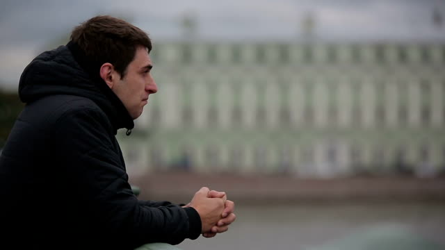 Sad man standing on bridge in center of St. Petersburg video