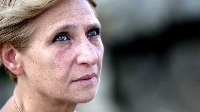 sorgliga medelålders kvinna vänder blicken mot himlen - 50 54 år bildbanksvideor och videomaterial från bakom kulisserna