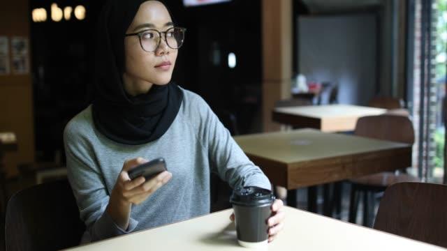 sorgliga muslimsk kvinna på fika - hijab bildbanksvideor och videomaterial från bakom kulisserna