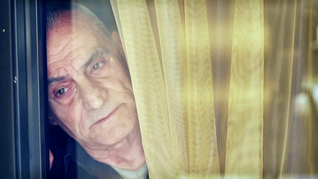 vídeos de stock e filmes b-roll de sad old and tired man looks what happens outside the window - old men window