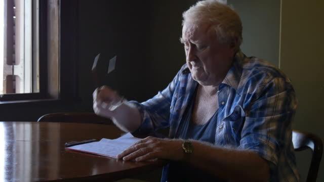 Triste vieillard âgée en retraite s'interrogeant sur la lettre à table - Vidéo