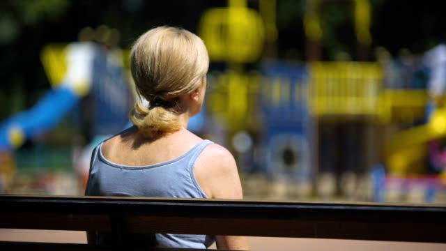 Sad old female sitting on playground bench and looking at children, infertility video