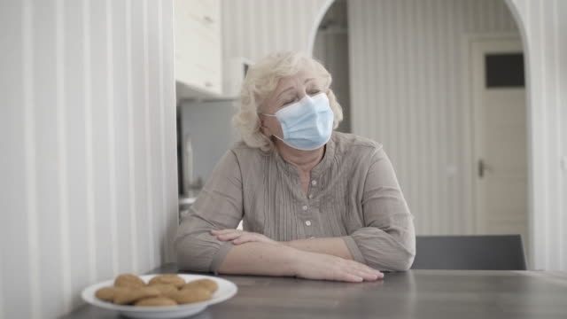 Sad old lady in protective mask thinking of problem at home, feeling lonely