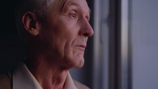 sad old man crying near window, suffering loneliness, abandoned by relatives - tylko jeden mężczyzna filmów i materiałów b-roll