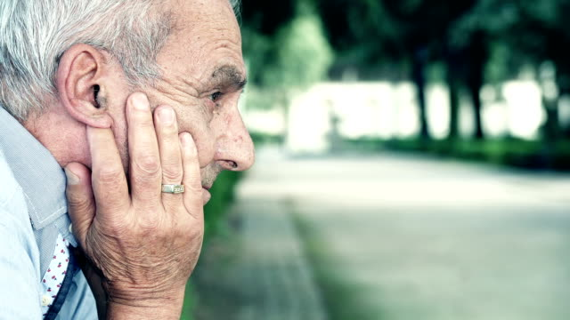 Sad old man reflected in a park holding his face with  hands video