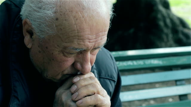 sad old man sitting on the bench sad old man sitting on the bench : outdoor footage of old sad man sitting alone in the park and thinking about his trouble depression land feature stock videos & royalty-free footage