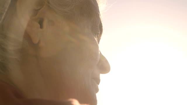 sad old woman in sunset - distrarre lo sguardo video stock e b–roll