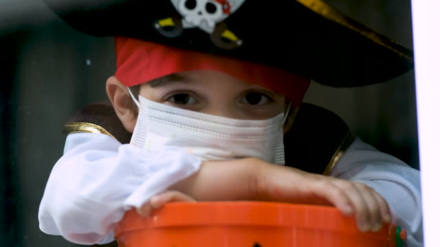 Sad pensive little boy wearing a halloween pirate costume and a protective face mask looking through a window holding a Jack o Lantern bucket Sad little boy wearing a halloween pirate costume and a protective face mask looking through a window holding a Jack o Lantern bucket halloween covid stock videos & royalty-free footage