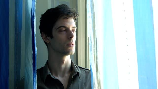 sad pensive young man with window natural light on his face - male eyes bildbanksvideor och videomaterial från bakom kulisserna