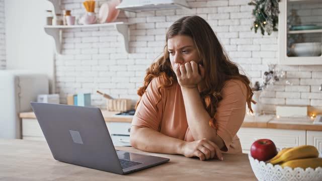 キッチンでラップトップコンピュータで働く悲しいプラスサイズの女性、オンラインショーや領収書を検索、接続の問題 - 体への関心点の映像素材/bロール