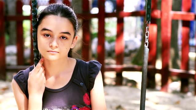 preteen triste ragazza seduta su altalena - preadolescente video stock e b–roll