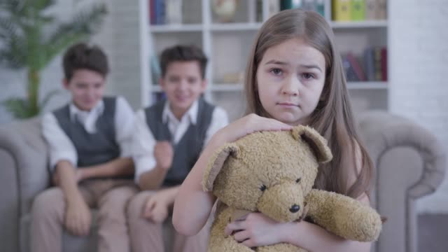Sad pretty Caucasian girl with teddy bear looking at camera as twin brothers pointing on her and laughing at the background. Childhood, bullying, lifestyle. Focused on foreground.