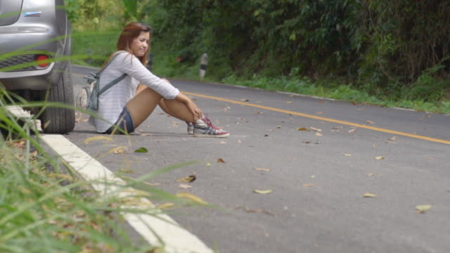 Sad pretty girl sitting on the road after car accident video