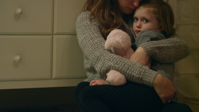 Sad, scared young girl with a stuffed animal being held by her mother in her room video