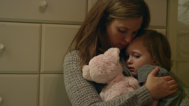 sad, scared young girl with a stuffed animal being held by her mother in her room - genitori video stock e b–roll