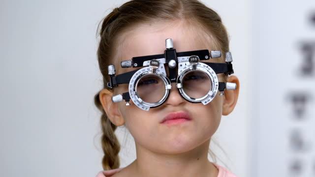 vidéos et rushes de écolière triste dans le cadre optique d'essai, l'essai de vue, la prescription de lunettes - réfracteur