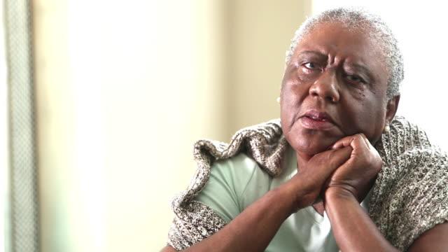 Sad senior African-American woman sitting at home