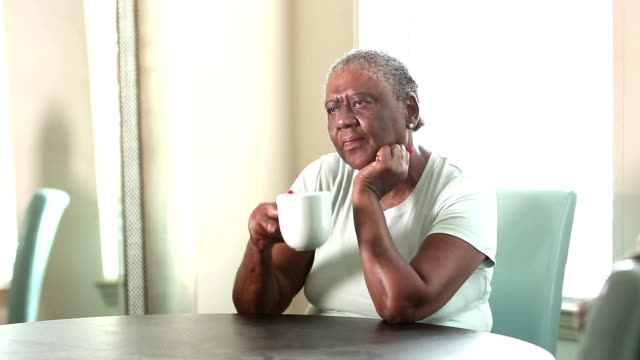 Sad senior African-American woman sitting at home