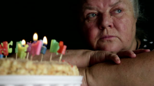 Sad senior woman looking at birthday cake with letter candles happy birthday video