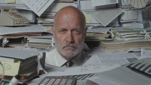 vidéos et rushes de homme d'affaires stressé triste sous beaucoup de paperasse - entassé