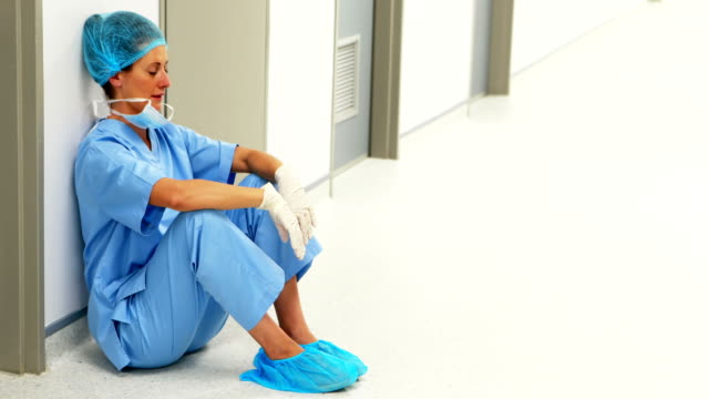 sad surgeon sitting on floor in corridor - nurse filmów i materiałów b-roll