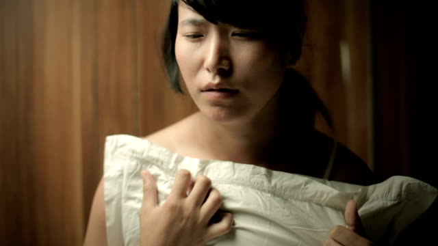 Sad teenage Asian girl crying with tears holding pillow. video