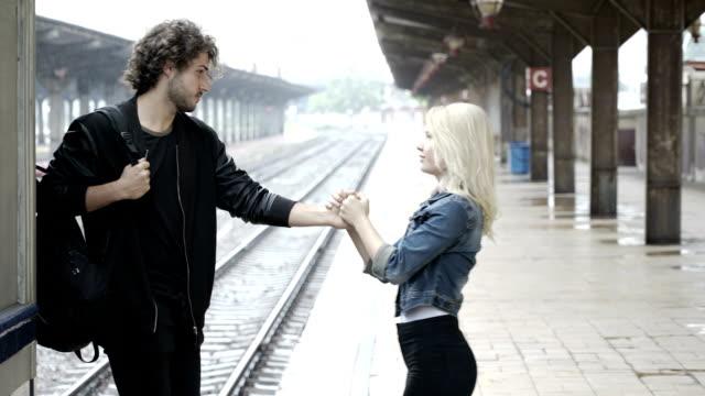 vídeos de stock, filmes e b-roll de casal de adolescente triste dizer adeus plataforma de estação de trem - despedida