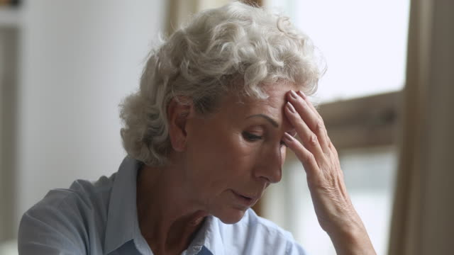 sad thoughtful older woman worried about health problems at home - solitario video stock e b–roll