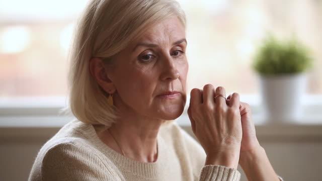 triste donna anziana premurosa che si sente sola preoccupata per i problemi - fragilità video stock e b–roll