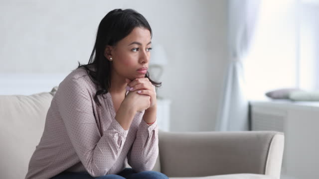 Sad thoughtful young african woman thinking of problems sit alone