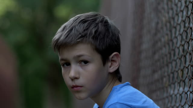 stockvideo's en b-roll-footage met triest overstuur misbruikt tiener jongen zit alleen, eenzame dakloze jongen, pijn op gezicht - portait background