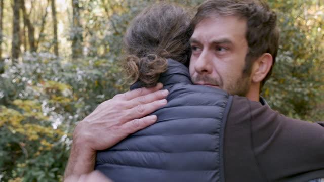 stockvideo's en b-roll-footage met triest, boos, huilende jonge man knuffelen een andere man buitenshuis - funeral crying