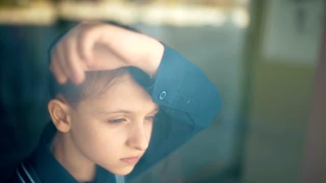 Sad upset tired unhappy kid standing near the window