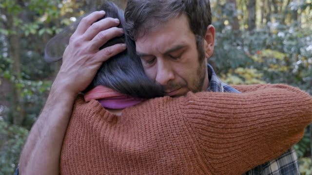 Sad, upset young man hugging a woman who is comforting him while outdoors
