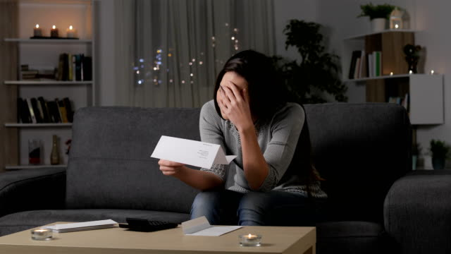 Sad woman complaining reading a letter in the night